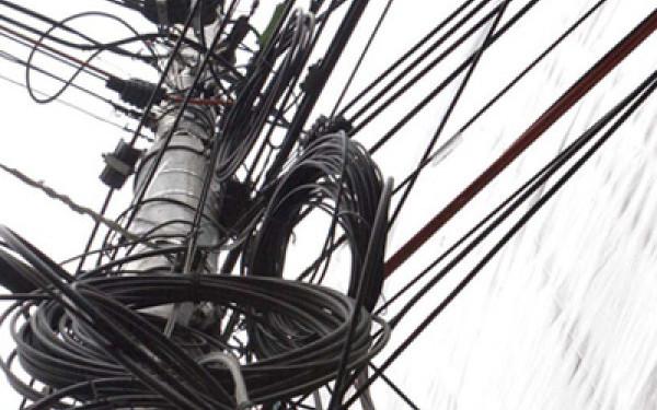 """Firmele """"rele"""" lasă cablurile atârnate pe stâlpii Timişoarei"""